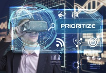 Business, Technology, Internet and network concept. Young businessman working in virtual reality glasses sees the inscription: prioritize